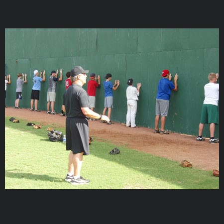 Tom House teaching on the field about pitching mechanics